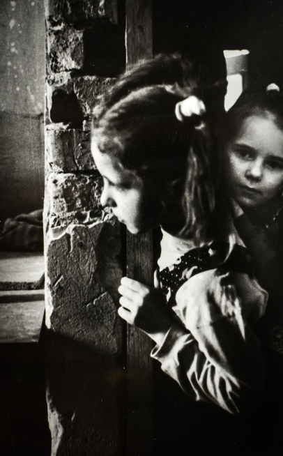 Two girls peeking around the corner of a dilapidated stone wall.