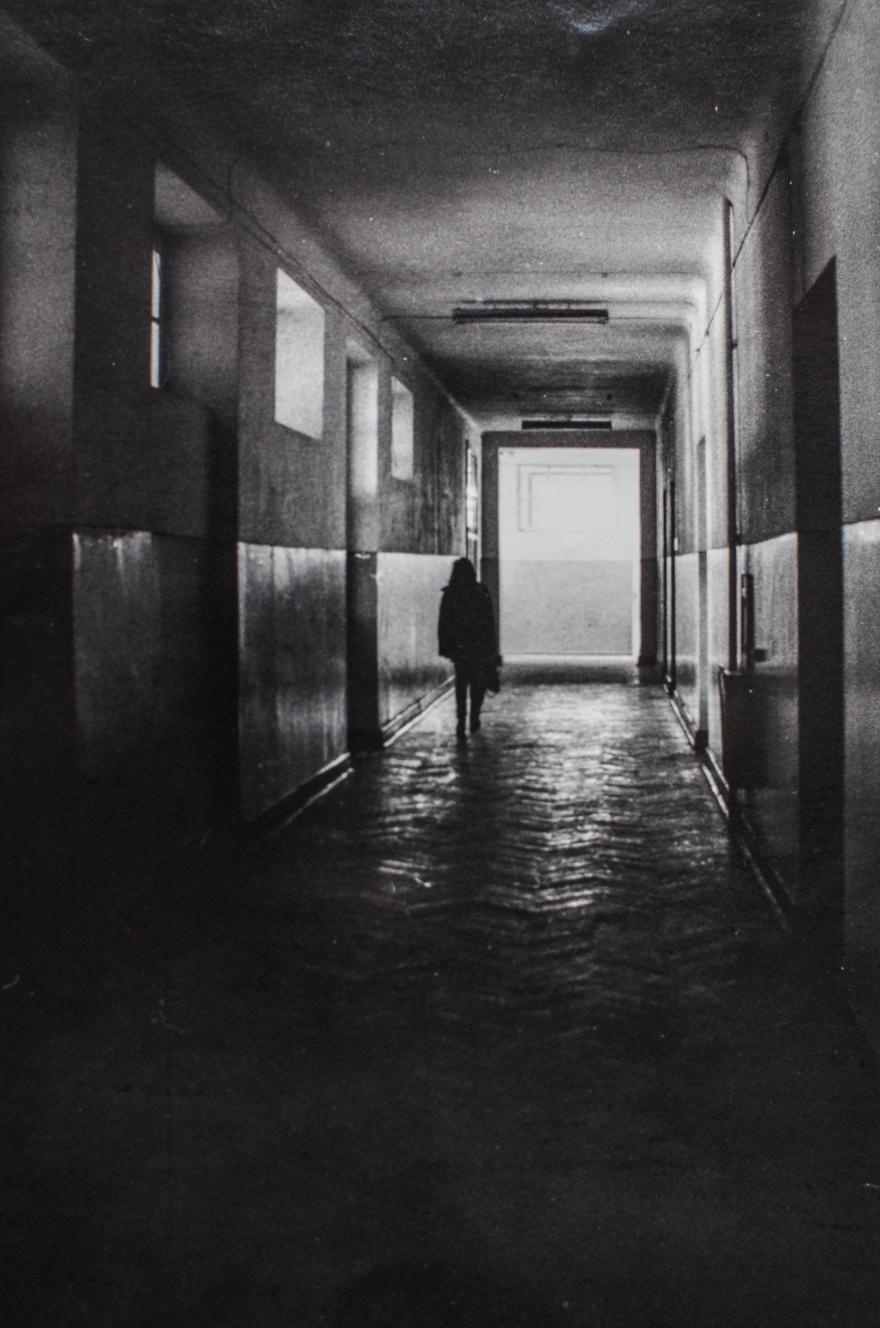 Black and white photograph of figure walking down a dark hallway to the foreground where there is a lit door